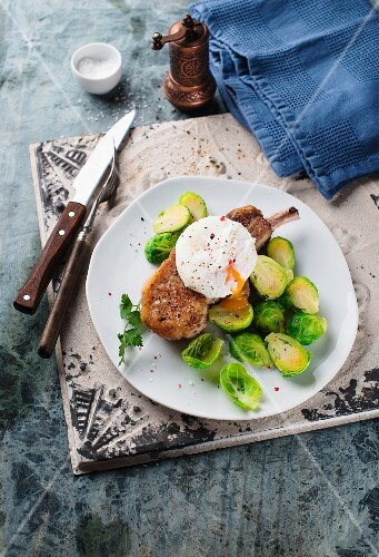 A pork chop with brussels sprouts and a poached egg