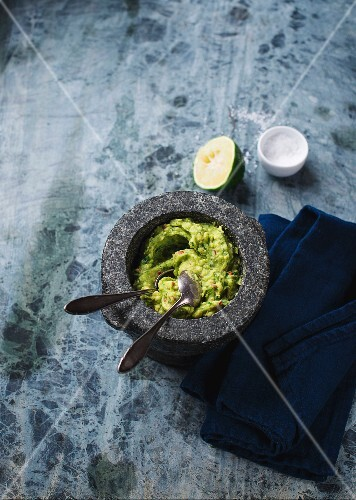 Guacamole in a mortar with spoons