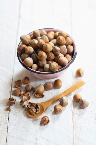 Hazelnuts in a bowl and next to it