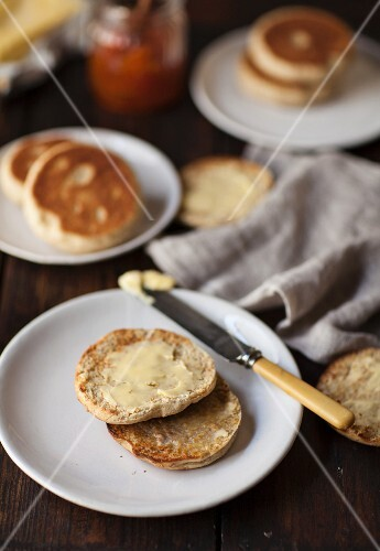 A toasted English muffin spread with butter