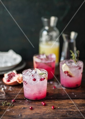 Pomegranate lemonade with thyme and ice cubes