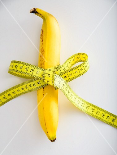 A banana tied with a tape measure on a white surface