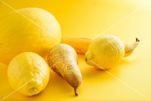 An arrangement of yellow fruits on a yellow surface