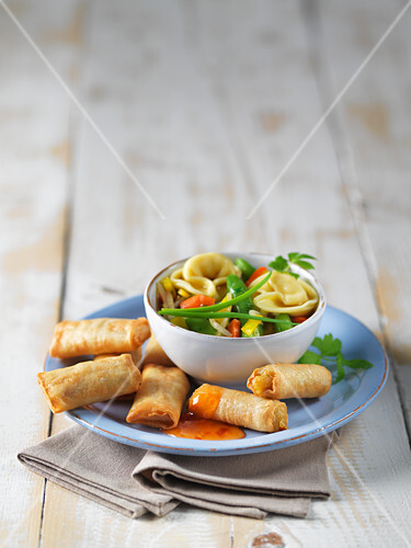 Mini spring rolls and vegetable soup on a plate