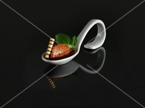Mousse au chocolat and plum sauce on a serving spoon