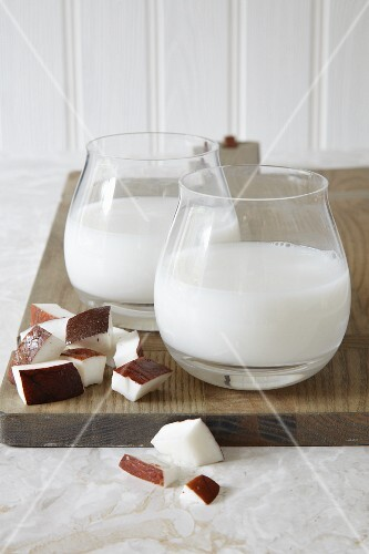 Two glasses of vegan coconut milk and pieces of coconut
