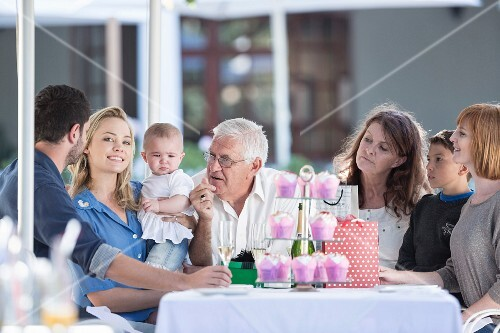 A multi-generational family celebrating a birthday at a table on a restaurant terrace
