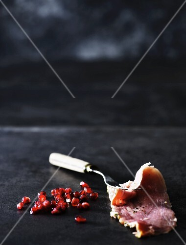 A slice of ham and pomegranate seeds