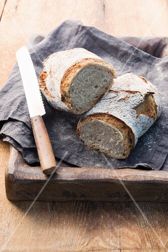 Two rustic loaves of bread on a linen cloth on a wooden tray with a bread knife