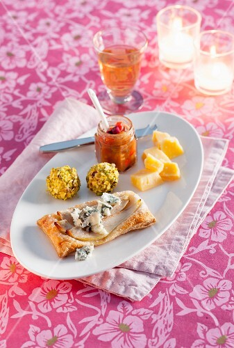 A Christmas dessert platter with goat's cheese truffles, a puff pastry with pears and blue cheese with pepper and date chutney
