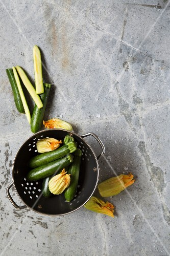 Courgette and courgette flowers in a colander