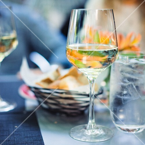 A glass of white wine outside on a table