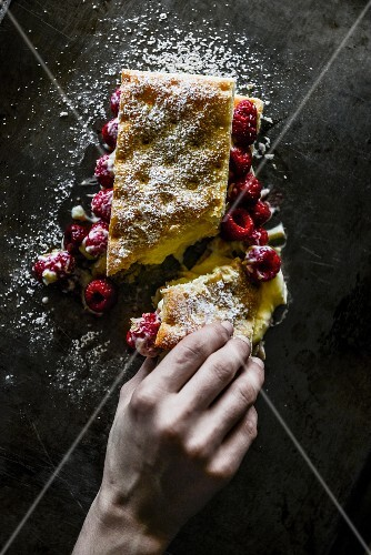 A hand reaching for a slice of raspberry cake