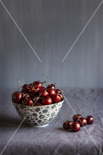 Cherries in a bowl and next to it