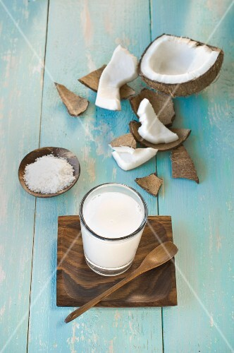 A glass of coconut milk, a broken coconut and grated coconut