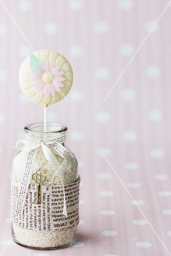 A carrot lolly decorated with a sugar flower in a jar of rice