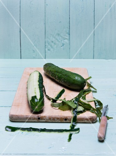 A peeled cucumber on a wooden board with a peeler and peel