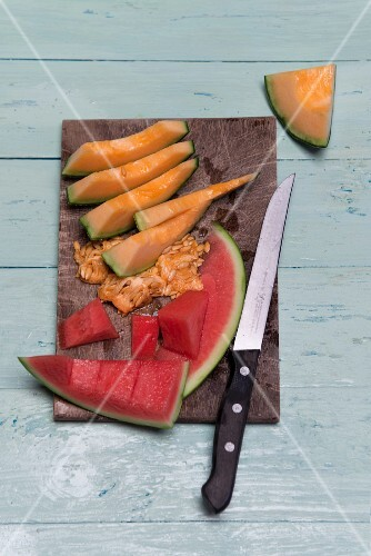 Slices of watermelon and cantaloupe melon on a wooden board