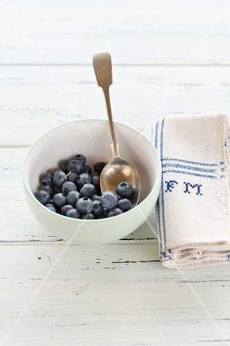 Blueberries in a white bowl with a napkin embroidered with initials