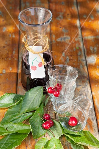 Carafe with hand-made label and glasses decorated with cherries