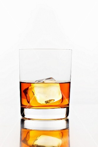 A glass of whiskey with an ice cube
