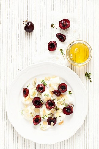 A plate of ricotta with fresh cherries, almonds, thyme and honey