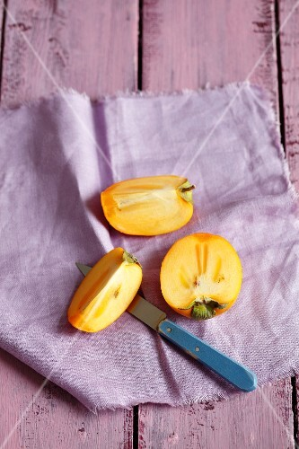 Persimmons, sliced, on a purple cloth