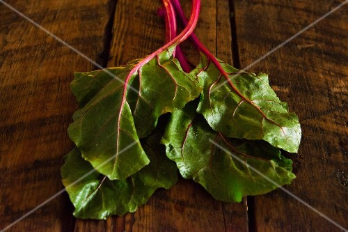 Chard leaves on wooden background