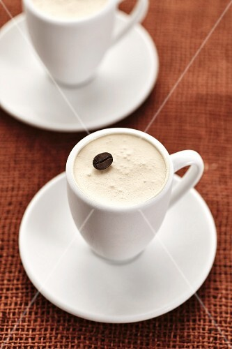 A coffee dessert garnished with a coffee bean in a mocha cup