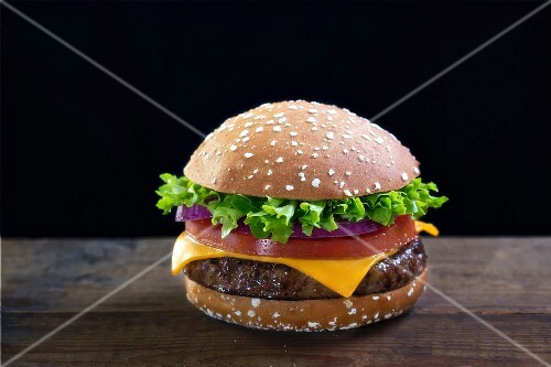 A cheeseburger with tomatoes, onions and lettuce