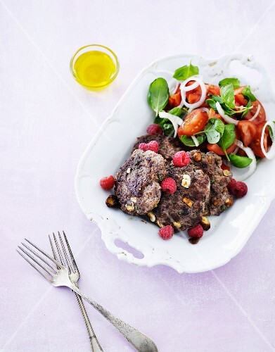Beef with nuts, olives, raspberries and tomato salad