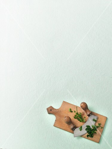 A mezzaluna with chopped parsley on a chopping board