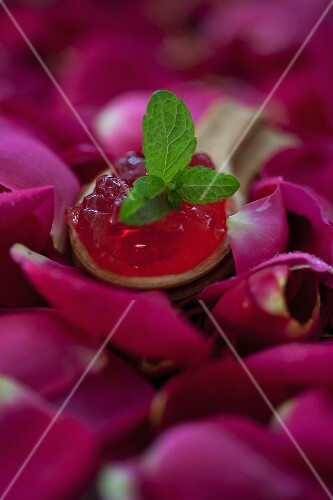Rose jelly on a biscuit spoon on rose petals