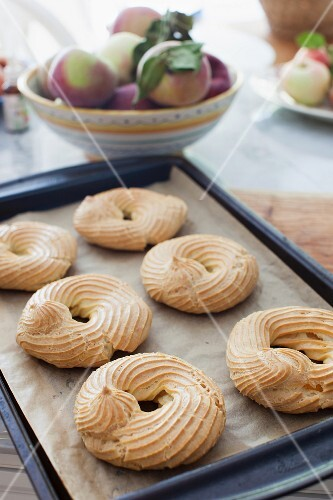 Baked choux pastry rings on a baking tray
