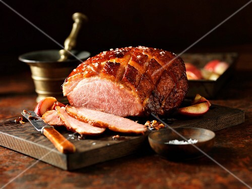 Roast ham, slices carved, on chopping board