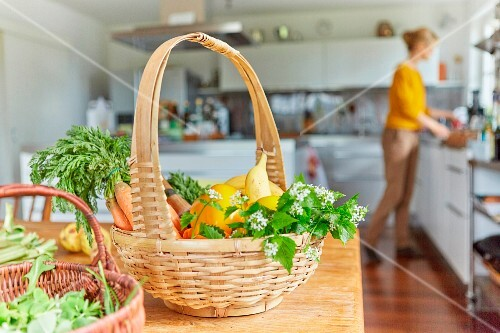 Baskets of fresh garden vegetables on a kitchen table with a woman in the background
