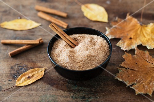 Sugar with cinnamon and cinnamon sticks in a bowl