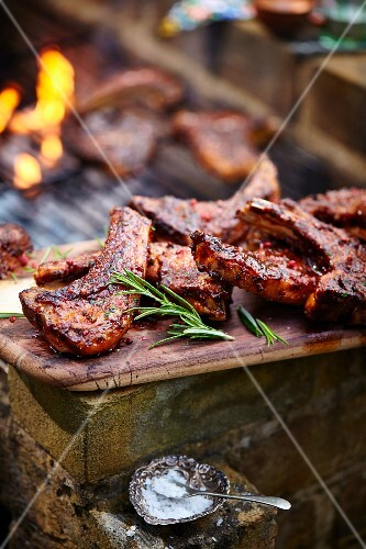 Grilled lamb chops on a wooden board next to a barbecue