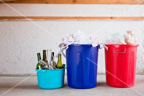 Waste separation: glass, paper and plastic in three different buckets