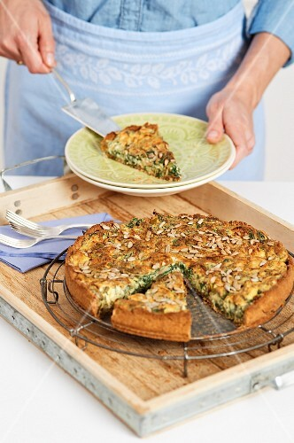 Stinging nettle and quark quiche with sunflower seeds being served