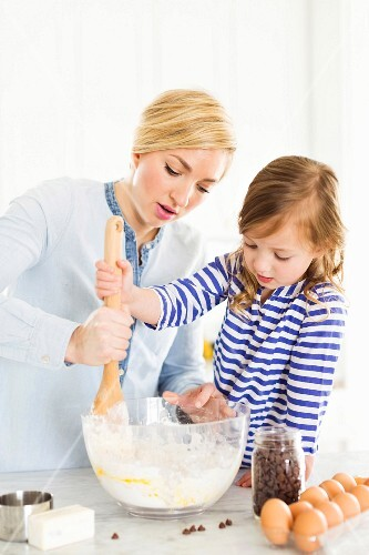 A mother and daughter stirring cake mixture