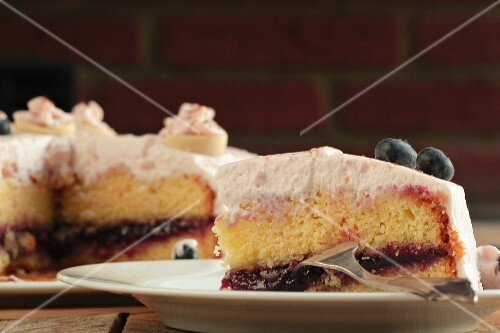A slice of blueberry cream cake with the rest of the cake in the background