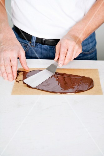 Chocolate leaves being made: liquid chocolate being spread on baking paper