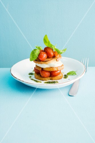 A stack of bread chips, tomatoes, mozzarella and pesto