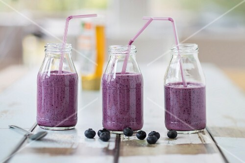 Three bottles of blueberry smoothies with straws