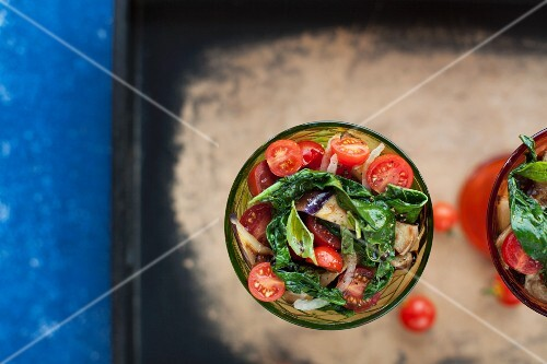 Tomato and aubergine salad with spinach and sweet onions in glasses