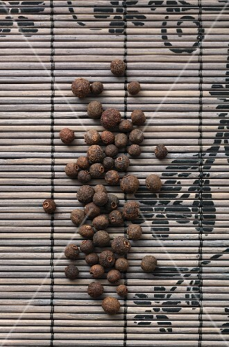 Allspice berries on a bamboo mat (seen from above)