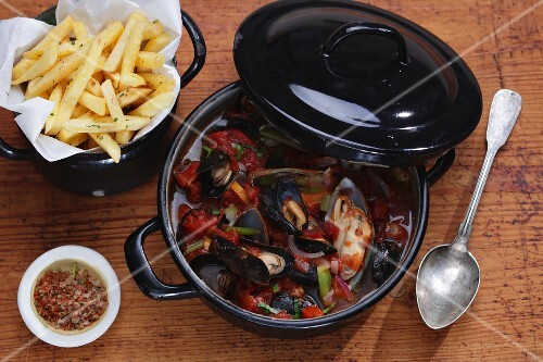 Mussel stew with chips on a wooden surface