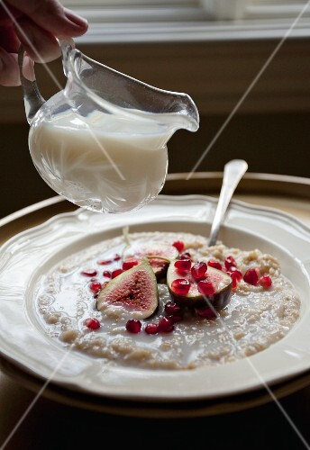 Milk being poured over porridge with figs and pomegranate seed