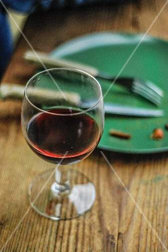 Glass of red wine next to an empty plate